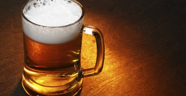 Mug of beer close up on wooden table